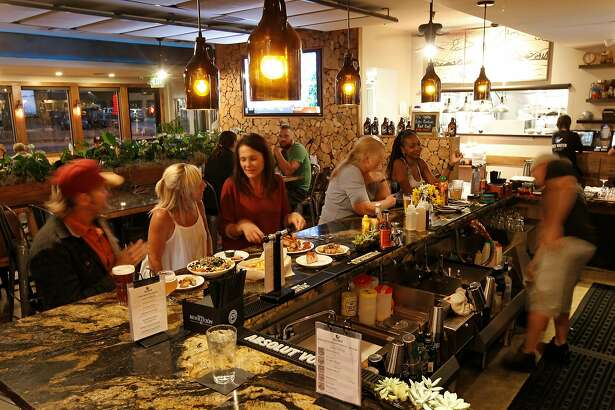 Debbie Brown, (second from left) the owner of theCold Water Brewery in South Lake Tahoe, Calif. talks with Mary Henderson on Thurs. August 30, 2018, at the bar.