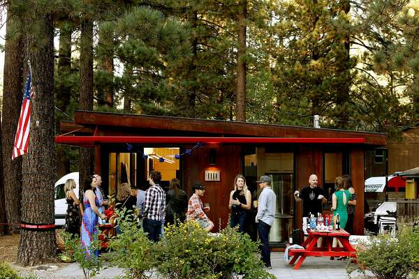 After work barbecues are common at the headquarters of Novus Select on Ski Run blvd. as seen on Thurs. August 30, 218 in South Lake Tahoe, California. Corey Rush, (left center) co-founder of Novus Select and Chris McNamara, (right center) founder of Outdoor Gear Lab Services and Chris's wife Viktoria, (center) enjoy the evening.