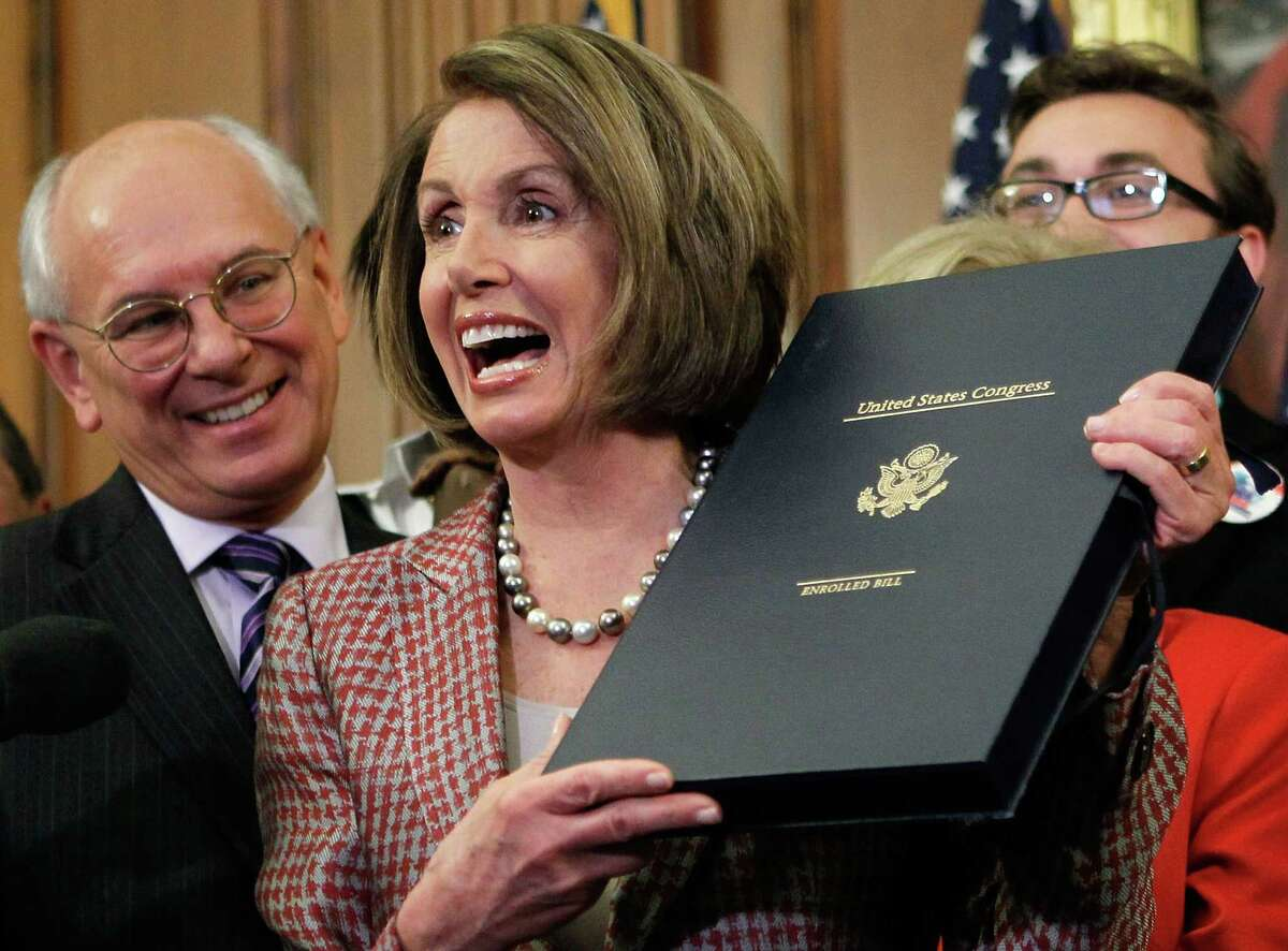 WASHINGTON - MARCH 26: U.S. Speaker of the House Rep. Nancy Pelosi (D-CA) (R) holds up the box that carries the revised Health Care and Education Reconciliation Act after she signed it during an enrollment ceremony as Rep. Paul Tonko (D-NY) (L) looks on March 26, 2010 on Capitol Hill in Washington, DC. The House passed the bill that completed heath care reform by a vote of 220 to 207.