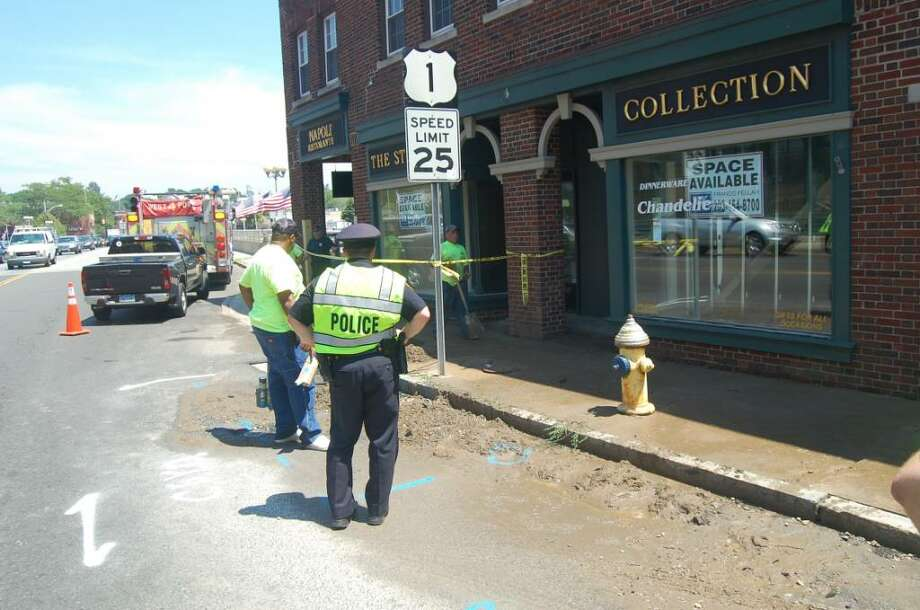 Westport police and fire crews coordinate with representatives from Aquarion Water Co. to respond to a water main break in downtown Westport at approximately 1 p.m. on Monday, July 12, 2010. The break - the second of the day - affected nine nearby customers and caused significant traffic delays on the Post Road. Photo: Anthony Karge / Westport News