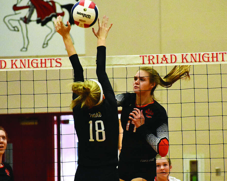 Edwardsville's Storm Suhre, right, slams a kill through the Triad block during the first game on Monday inside Rich Mason Gymnasium in Troy. Photo: Matthew Kamp