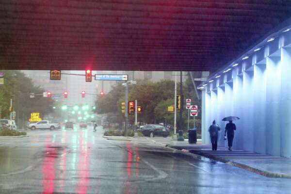 As rain falls, pedestrians walk under the Interstate 37 overpass at East Commerce Street on Sunday. Over the weekend, San Antonio International Airport received nearly 4 inches of rain. Monday's showers dropped about an additional half-inch.
