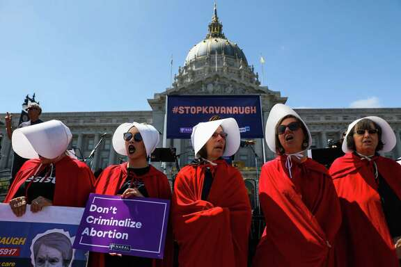 "Women dressed in ""Handmaid's Tale"" costumes line up at the Unite For Justice rally where demonstrators protested U.S. Supreme Court nominee Brett Kavanaugh and promoted women's equality outside City Hall in San Francisco on Sunday, August 26, 2018."