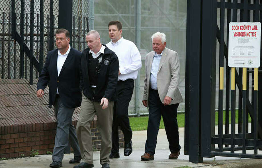 Jason Van Dyke (second from right), a Chicago police officer charged with murder in the 2014 shooting of black teenager Laquan McDonald, walks out of Cook County Jail in Chicago with his father, Owen (right) after posting bond Thursday following a court hearing in which a judge ruled he won't be jailed for giving interviews in violation of his bail terms. Van Dyke is charged with first-degree murder, aggravated battery and official misconduct. Photo: Teresa Crawford | AP
