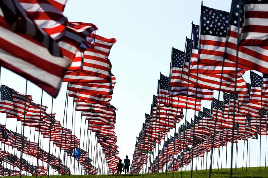 Bianca Burton, center left, and Erin Schultheis walk around the Pepperdine University's annual display of flags honoring the victims of the 9/11 terrorist attacks, Monday, Sept. 10, 2018, in Malibu, Calif. Terrorists used hijacked planes to crash Sept. 11, 2001, into the World Trade Centers, the Pentagon and a field in Pennsylvania. Nearly 3,000 people were killed in the attacks. (AP Photo/Jae C. Hong) Photo: Jae C. Hong / Copyright 2018 The Associated Press. All rights reserved.