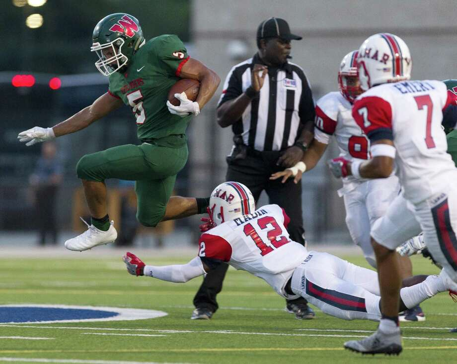 The Woodlands running back Bryeton Gilford (5) leaps past Lamar defensive back Matthew Mabin (12) during the first quarter of a non-district high school football game at Woodforest Bank Stadium on Thursday, Sept. 6, 2018, in Shenandoah. Photo: Jason Fochtman, Houston Chronicle / Staff Photographer / © 2018 Houston Chronicle