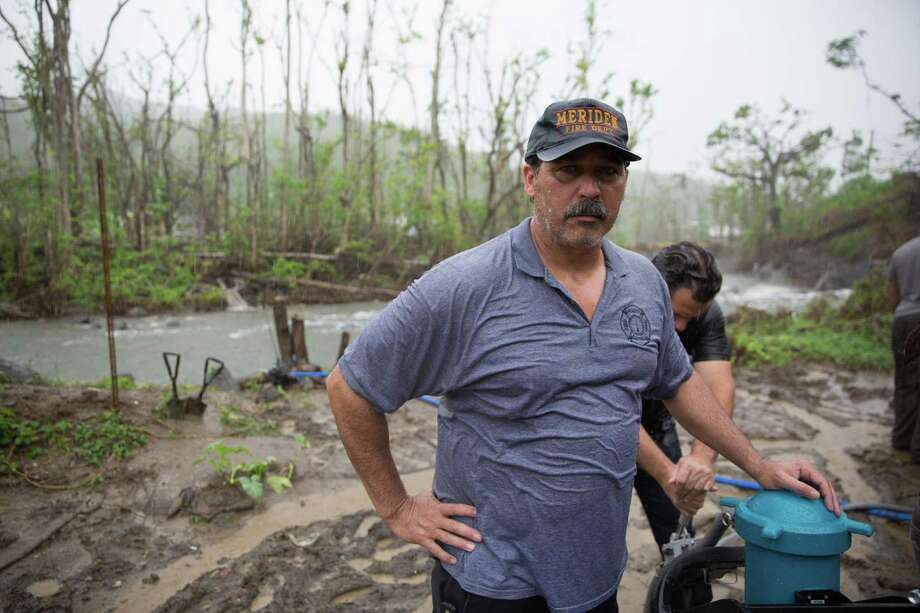 """Danny Torres has worked for the fire department in Meriden for decades and has family across Puerto Rico. He was part of team of Connecticut veterans and volunteers — self-described as the Puerto Rican """"water dogs"""" — pumping water from a river in Salinas, Puerto Rico, through a mobile filtration and purification system for residents there to drink after the hurricane. Photo: Ryan Caron King For Connecticut Public Radio"""