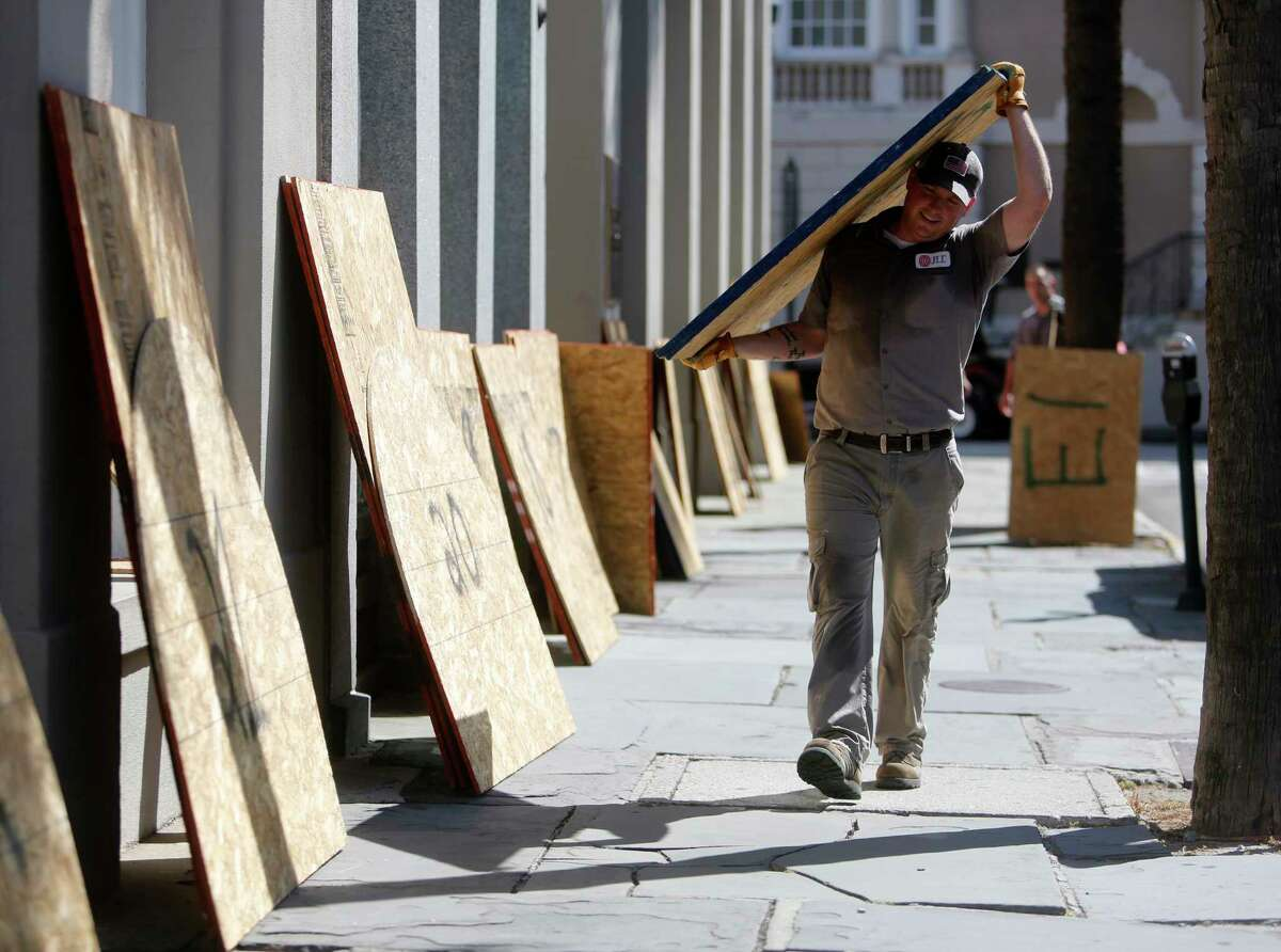 Preston Guiher carries a sheet of plywood as he prepares to board up a Wells Fargo bank in preparation for Hurricane Florence in downtown Charleston, S.C., Tuesday, Sept. 12, 2018.