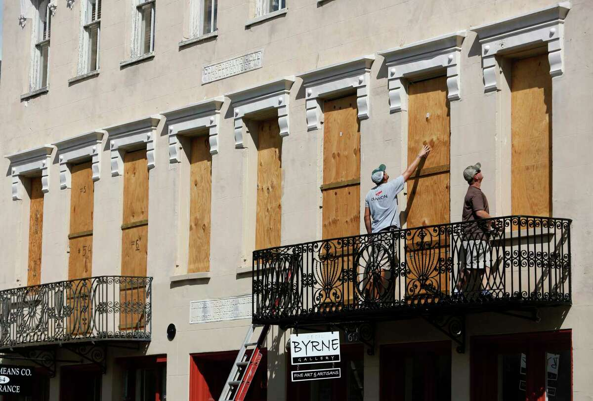 Derek Mundy, left, and Kris Crouse boards up the Confederate House in preparation for Hurricane Florence in downtown Charleston, S.C., Tuesday, Sept. 12, 2018.