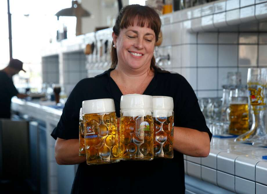 Bartender Christina Johnson carries liter steins of beer to a table at Radhaus beer hall at Fort Mason. Photo: Paul Chinn / The Chronicle