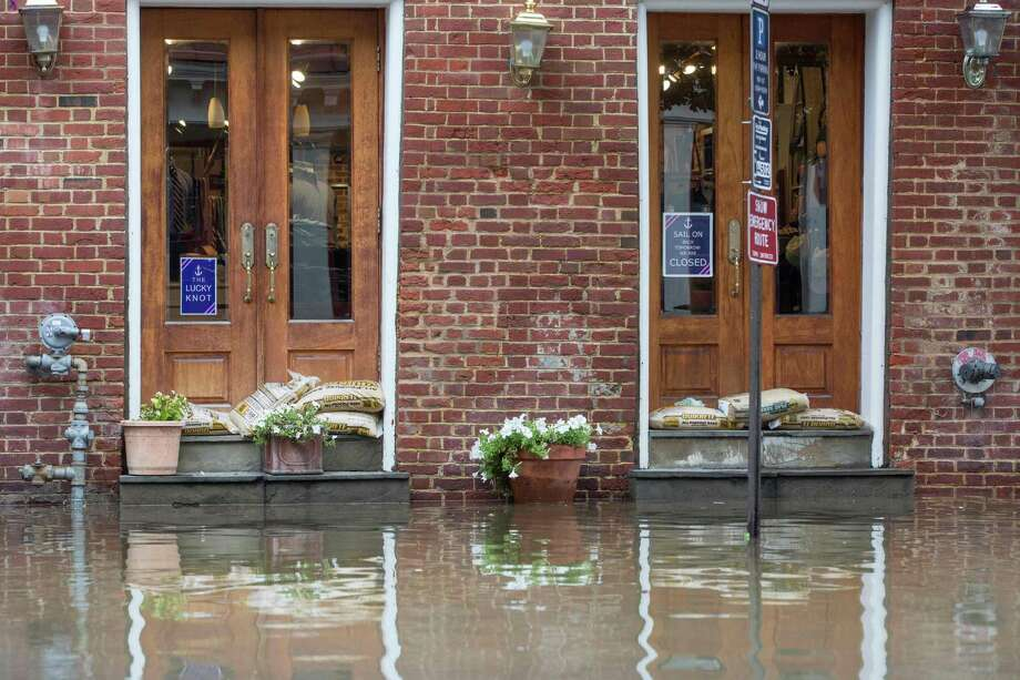 Sandbags sit in doorways as water floods outside buildings in Old Town Alexandria, Va., on Tuesday. More than a million people were under evacuation orders in the eastern United States Tuesday, where powerful Hurricane Florence threatened catastrophic damage. Photo: Zach Gibson / AFP / Getty Images / AFP or licensors