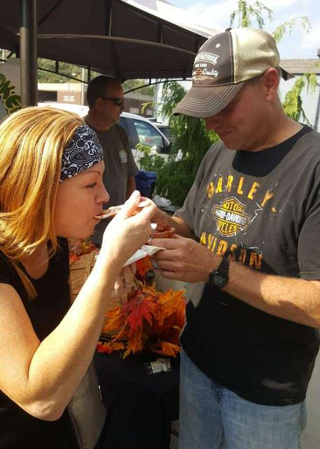 Two attendees at last year's Chili Cook-Off sample smoked chili from Olive Oil Marketplace. Photo: Telegraph File Photo