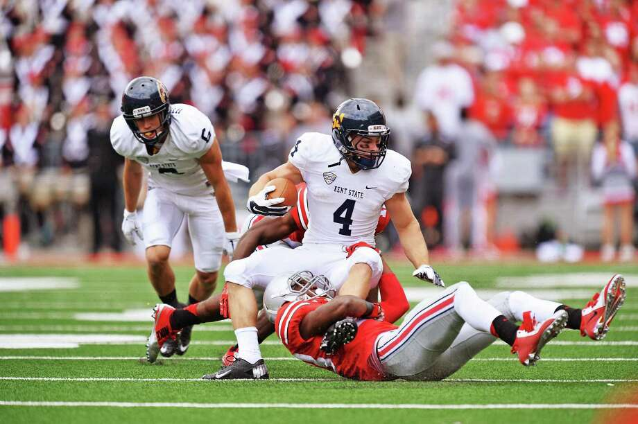 COLUMBUS, OH - SEPTEMBER 13: Nick Holley #4 of the Kent State Golden Flashes is dragged down by Tyvis Powell #23 of the Ohio State Buckeyes in the first quarter at Ohio Stadium on September 13, 2014 in Columbus, Ohio. (Photo by Jamie Sabau/Getty Images) Photo: Jamie Sabau / Getty Images / 2014 Getty Images