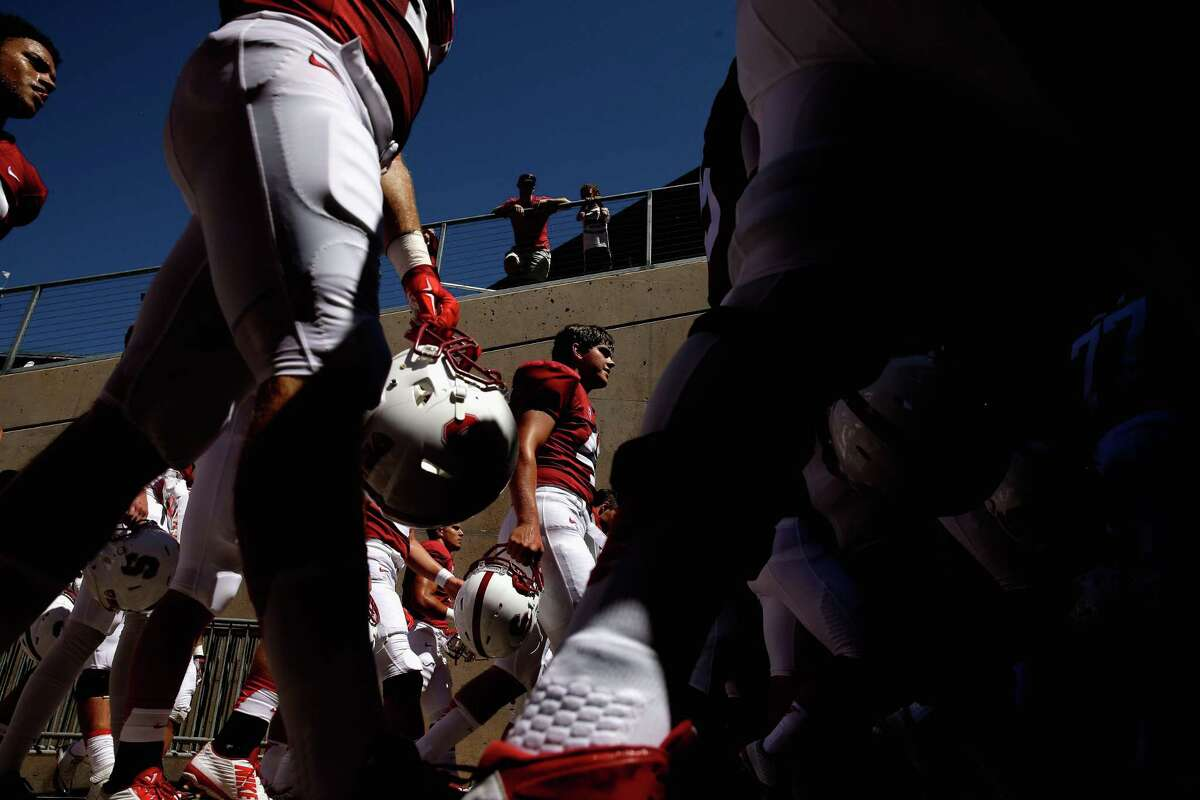 PALO ALTO, CA - AUGUST 30: Alex Robinson #47 (center) of the Stanford Cardinal walks back into the lockerroom with his teammates after warming up before their game against the UC Davis Aggies at Stanford Stadium on August 30, 2014 in Palo Alto, California. (Photo by Ezra Shaw/Getty Images)