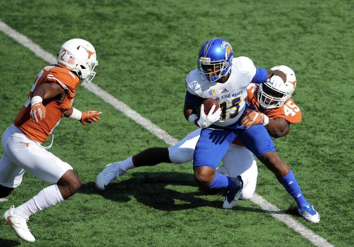 AUSTIN, TX - SEPTEMBER 09: San Jose State WR Tre Hartley (15) is tackled by Texas defenders Anthony Wheeler (45) and Kris Boyd (2) during game between the Texas Longhorns and the San Jose State Spartans on September 9, 2017 at Darrell K Royal-Texas Memorial Stadium in Austin, TX. The Texas Longhorns defeated the San Jose Spartans 56 - 0. (Photo by John Rivera/Icon Sportswire via Getty Images)
