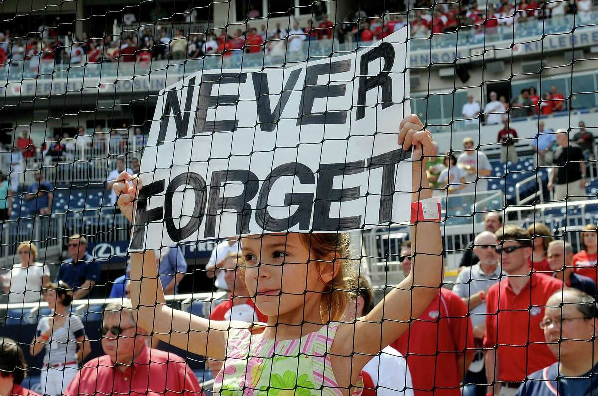 WASHINGTON, DC - SEPTEMBER 11: A fan holds up a sign during the moment of silence in remembrance of the ten year anniversary of the attacks on 9-11 before the game between the Washington Nationals and the Houston Astros at Nationals Park on September 11, 2011 in Washington, DC.
