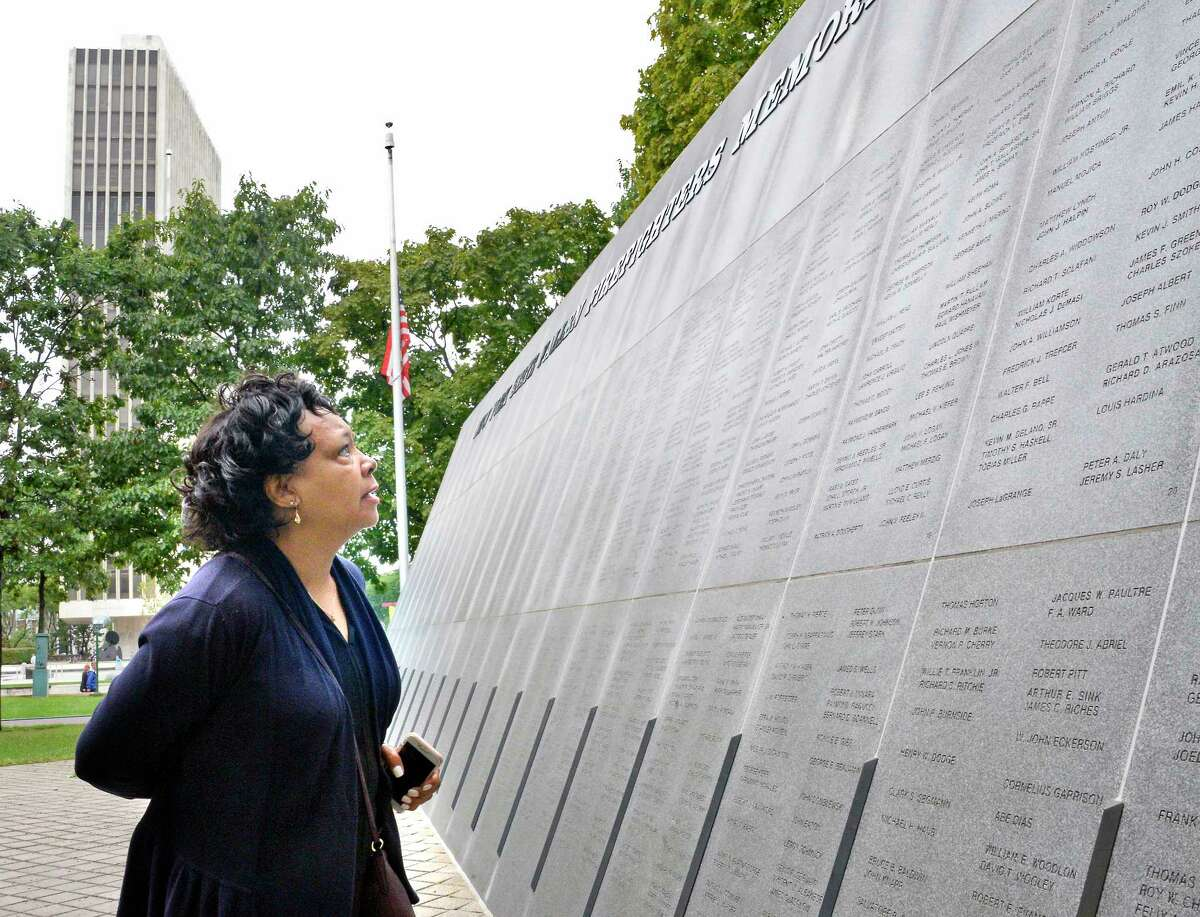 Barbara Croskery of Delmar looks for names of firefighters who died following the September 11 attacks in NYC at the New York State Fallen Firefighters Memorial Tuesday Sept. 11, 2018 in Albany, NY. (John Carl D'Annibale/Times Union)
