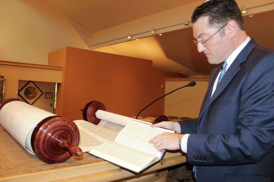 Rabbi Matthew Berger explains the Torah's significance for the Congregation Beth Shalom of The Woodlands, which is a reformed Jewish congregation. Berger said that throughout each Jewish calendar year, the congregation reads through the entire Torah. Photo: Jane Stueckemann / Jane Stueckemann