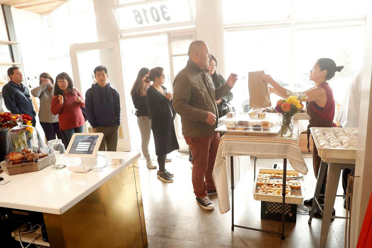 Kate Campesino-Wong hands out an order during Breadbelly's pop-up stand at Andytown Roastery in San Francisco, Calif. on Sunday, September 9, 2018.