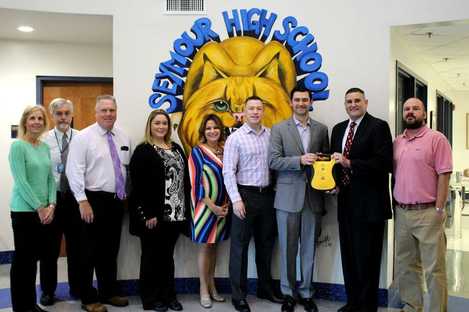 An automated external defibrillator was donated Nov. 30 to Seymour High School by the At A Heartbeat Foundation. From left, Teacher Cathy Federowicz; Principal Jim Freud; Assistant Superintendent of Schools Rick Beldin; Tara Yusko, athletic director; state Rep. Nicole Klarides-Ditria, R-105; Matt Gead, foundation board member; Mike Papale, foundation president, founder; Superintendent of Schools Michael Wilson; Aaron Paluck, teacher, boys soccer coach. Photo: Contributed Photo / File