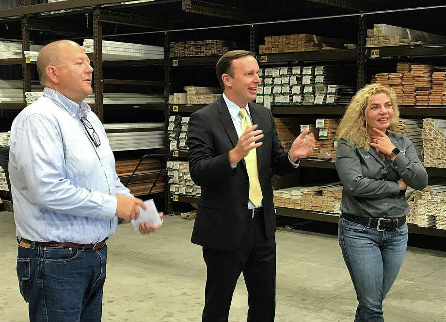 U.S. Sen. Chris Murphy, D-Conn., center, talks to Glenn Albee, president of Ridgefield Supply Co., and Margaret Price, owner and CEO of RSC, in the lumberyard at Ridgefield Supply Co. on Tuesday. Photo: Chris Bosak / Hearst Connecticut Media / The News-Times