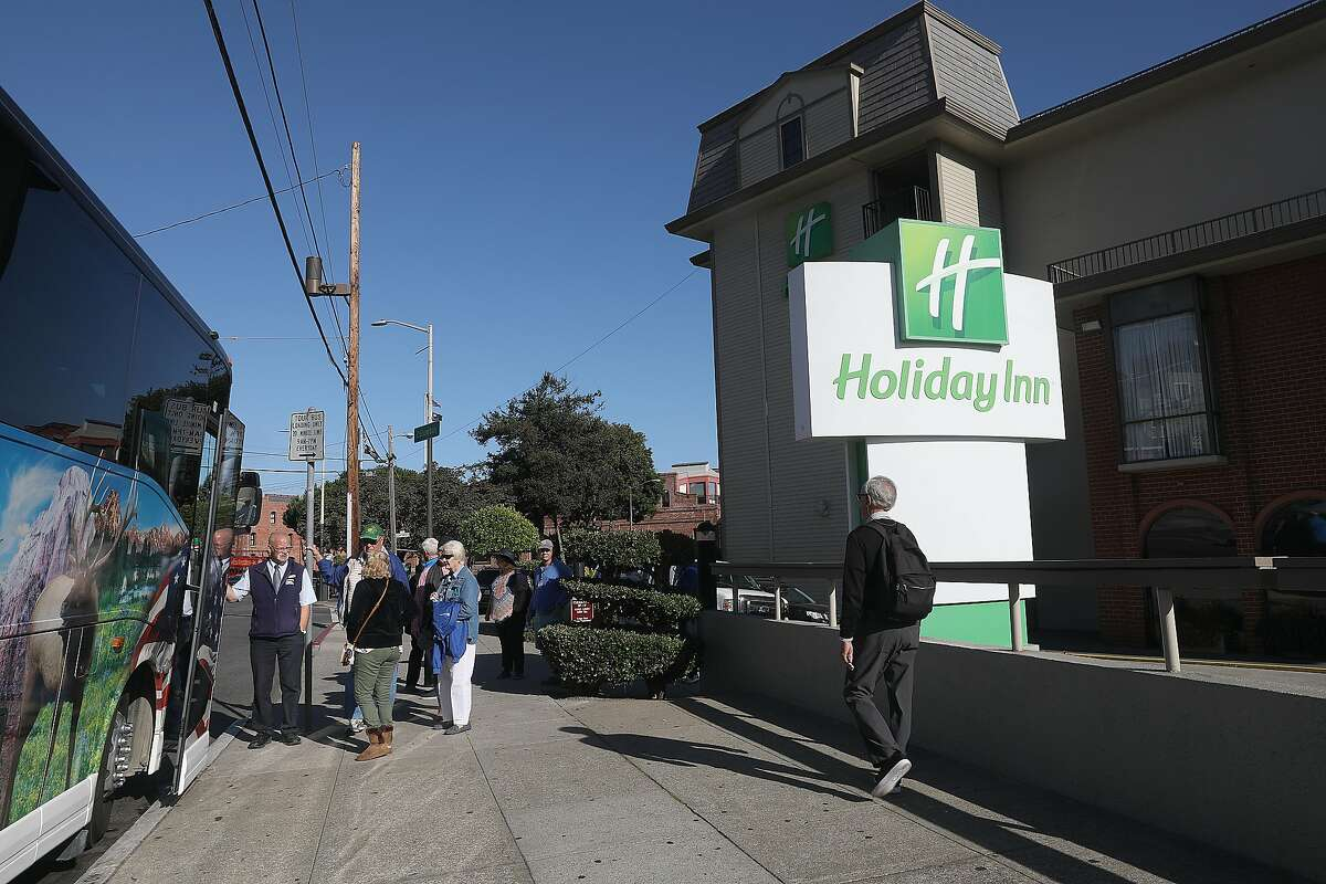 Tour bus picks up travelers from the Holiday Inn Fisherman's Wharf at 1300 Columbus St. where 168 employees will be laid off on Tuesday, Sept. 11, 2018 in San Francisco, Calif.