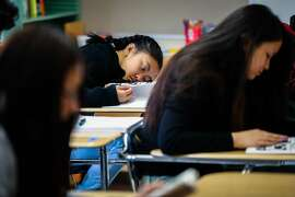 Makisha Brogan (center) puts her head on her desk� during a class at Phillip and Sala Burton High School in San Francisco, California, on Monday, Sept. 10, 2018. Gov. Gavin Newsom has a decision to sign or veto a bill that would require later start times for middle and high school students.