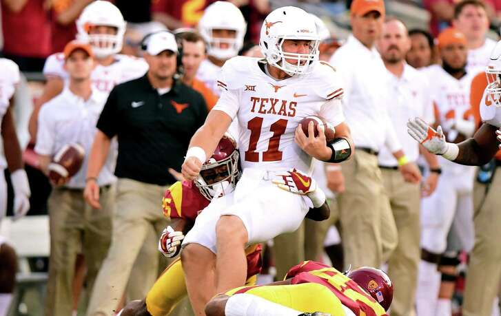 LOS ANGELES, CA - SEPTEMBER 16: Sam Ehlinger #11 of the Texas Longhorns is tackled by Jack Jones #25 and Uchenna Nwosu #42 of the USC Trojans during the first quarter at Los Angeles Memorial Coliseum on September 16, 2017 in Los Angeles, California. (Photo by Harry How/Getty Images)