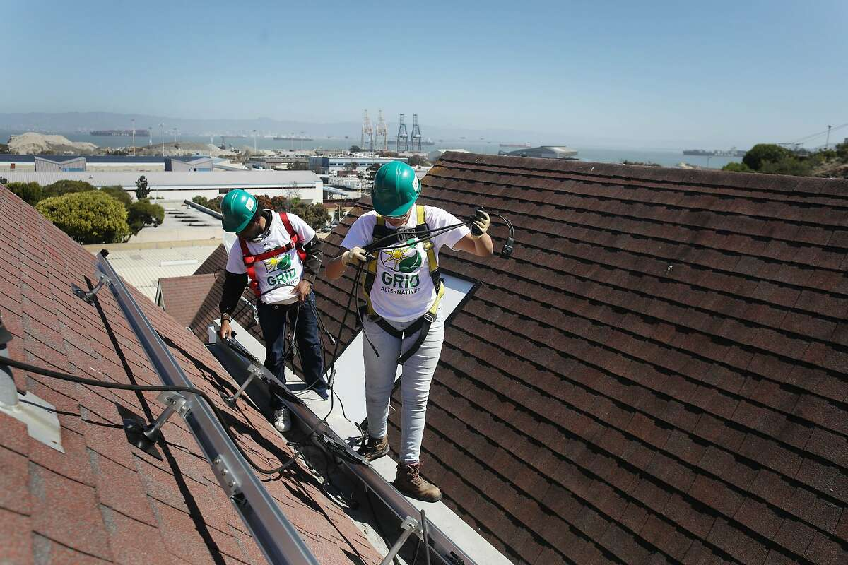 Chris James (l to r) and Lilliana Ruby Beltran, both with Young Community Developers job training program, work on Mike Aguayo's roof installing microinverters during a solar installation on Tuesday, September 11, 2018 in San Francisco, Calif.