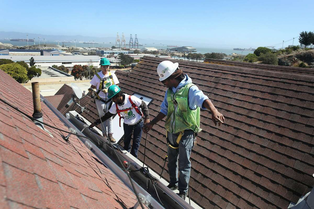 Brian Simmons (right), Grid Alternatives lead solar installation supervisor, works with Lilliana Ruby Beltran (left), with the Young Community Developers job training program and Chris James (center), with the Young Community Developers job training program, as they install microinverters during a solar installation on Mike Aguayo's roof on Tuesday, September 11, 2018 in San Francisco, Calif.