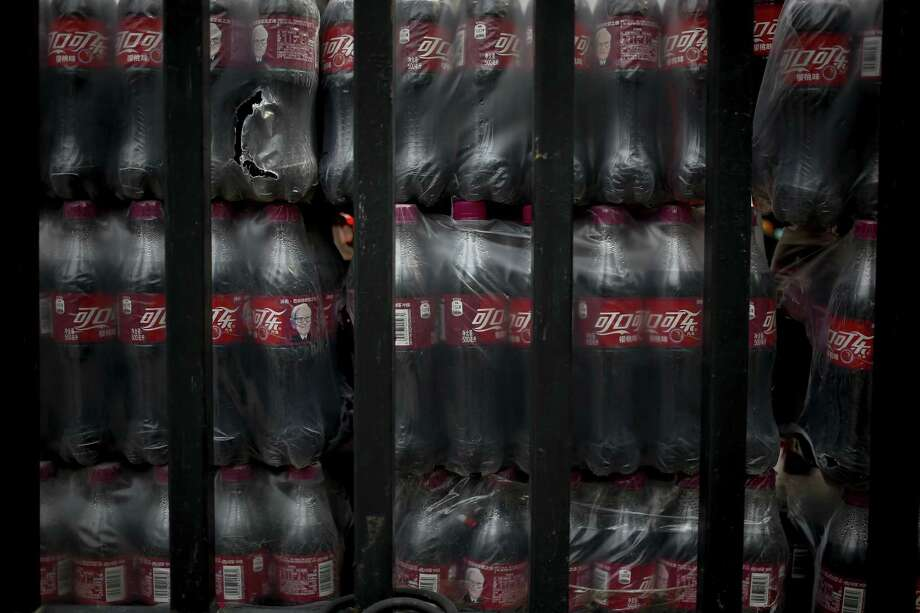 Bottles of Cherry Coca-Cola with portraits of Berkshire Hathaway Chairman and CEO Warren Buffett are stacked behind a fence in Beijing, Tuesday, Sept. 11, 2018. China on Monday promised retaliation if U.S. President Donald Trump escalates their tariff battle, raising the risk Beijing might target operations of American companies as it runs out of imports for penalties. Photo: Andy Wong /Associated Press / Copyright 2018 The Associated Press. All rights reserved.