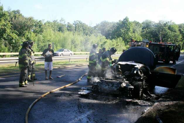 Members of the Fairfield Fire Department extinguish a car fire on the Merritt Parkway on Sunday. The Audi R8 belonged to a Powerball winner from Newington. According to reports, Rahul Patel, of Newington, was driving the car, only a week old, northbound on the parkway around 9 a.m., when, between exit 46 and 47 in Fairfield, he looked up in the rearview mirror and saw smoke. Photo: Contributed Photo\Fairfield Fire Department / Connecticut Post Contributed