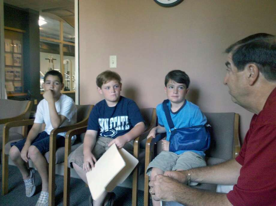 A petition started by three boys, from left, John McMillian, Luke Sohigian and Gus Bochanis, asks the Parks and Recreation Commission to reconsider a long-standing policy that bans boogie boards, skim boards, rafts, balls or any inflatable object in the water along a substantial stretch between Penfield and Jennings beaches. Here, the boys discuss their petition with Gerry Lombardo, director of Parks and Recreation, at right. Photo: Contributed Photo / Fairfield Citizen