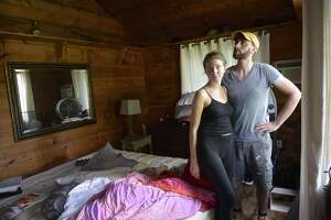 The Gaylordsville home of Alexander Quinn and Ashleigh Buccellato stand in the bedroom of the Gaylordsville home which was severely damaged Tuesday night when a tree fell through the roof causing the house to catch fire. Wednesday, September 5, 2018, in Gaylordsville, Conn.