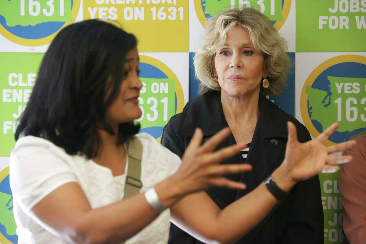 Actress and activist Jane Fonda listens as U.S. Rep. Pramila Jayapal speaks to volunteers during a campaigning event for Initiatives 1639 and 1631, which address gun safety and clean energy respectively, in the University District. Both are outspoken critics of President Trump and active in impeachment cause.