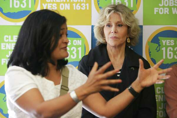 Actress and activist Jane Fonda listens as U.S. Rep. Pramila Jayapal speaks to volunteers during a campaigning event for Initiatives 1639 and 1631, which address gun safety and clean energy respectively, in the University District, Tuesday, September 11, 2018, before going out canvassing in the area.