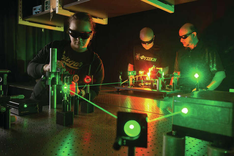SIUE students Nicole Lindsey, left, and Ronald Taylor with physics professor Abdullatif Hamad in laser lab. Photo: SIUE Photo