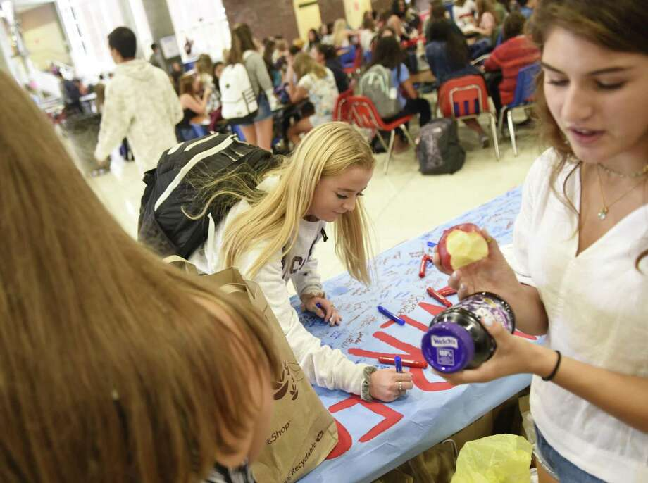 Sophomore Hailey Hires signs her name as GHS HEROES Club co-President senior Katie Turk, right, checks the date on her donation at the 9/11 Food Drive for Neighbor to Neighbor at Greenwich High School in Greenwich, Conn. Tuesday, Sept. 11, 2018. Sponsored by Roots & Shoots and the GHS HEROES Club, the food drive, now in its ninth year, collected several hundred nonperishable food items to be donated to the local nonprofit Neighbor to Neighbor. Photo: Tyler Sizemore / Hearst Connecticut Media / Greenwich Time