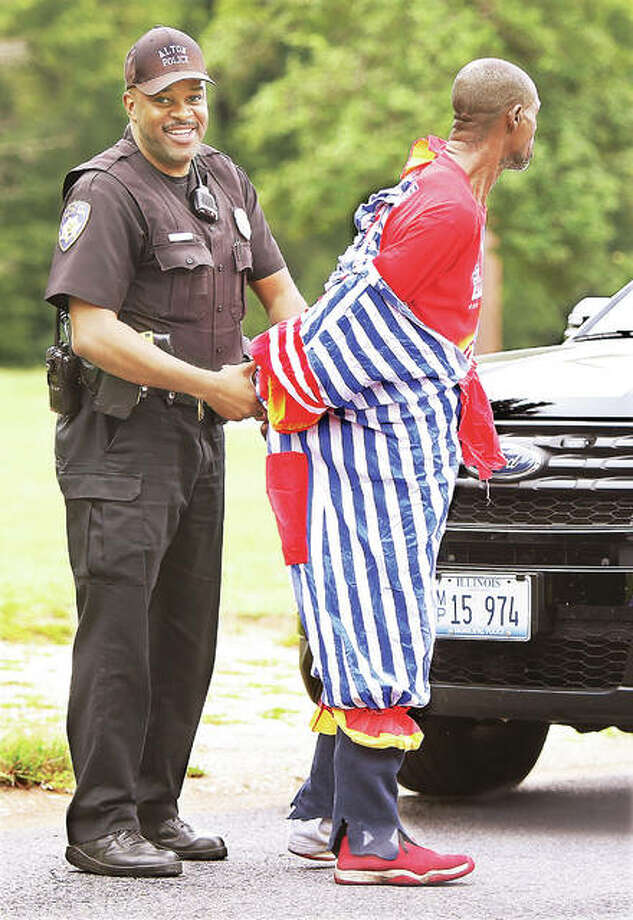 A normally very serious Alton police officer Tony Bumpers couldn't help but smile Friday as he arrested Ronald M. Singleton, 54, dressed in a clown costume after he was allegedly kicking on the door of a vacant business on Washington Avenue. The very next day, Saturday, apparently dressed in a clown suit again, Singleton was arrested in the 1800 block of Central Avenue on a felony charge of criminal damage to property. Photo: John Badman | The Telegraph