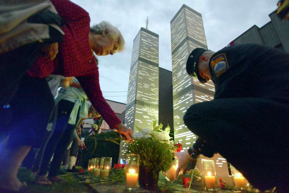 Olga Chagaris of Stamford, at left, places flowers at the base of eight-foot steel replicas of the Twin Towers in front of the Woodside Fire Station on Washington Blvd. as Stamford firefighter Roman Balzar lights tribute candles following a September 11th Remembrance Ceremony in Stamford, Conn. on Tuesday, Sept. 11, 2018. Photo: Matthew Brown, Hearst Connecticut Media / Stamford Advocate