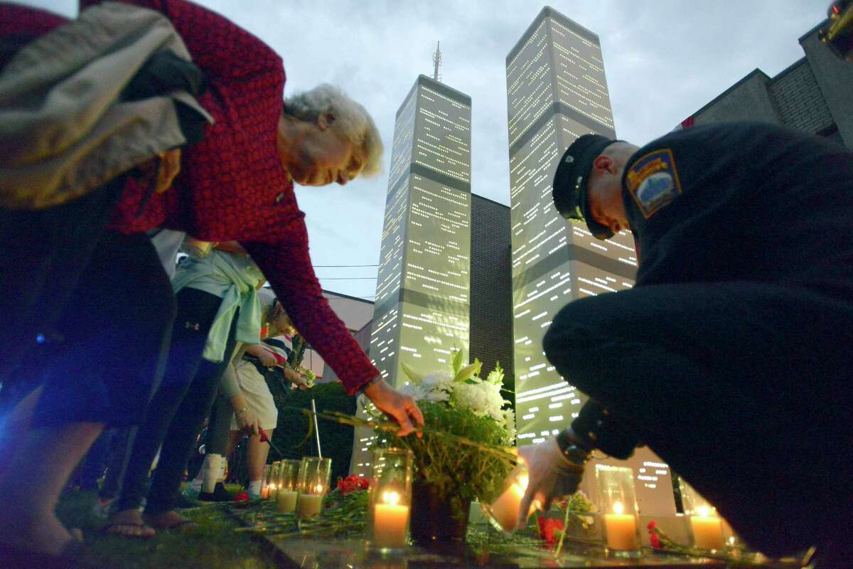 Olga Chagaris of Stamford, at left, places flowers at the base of eight-foot steel replicas of the Twin Towers in front of the Woodside Fire Station on Washington Blvd. as Stamford firefighter Roman Balzar lights tribute candles following a September 11th Remembrance Ceremony in Stamford, Conn. on Tuesday, Sept. 11, 2018.