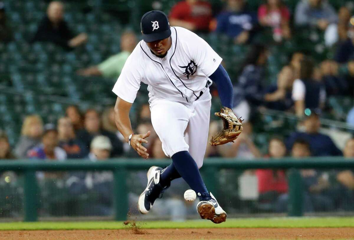 Detroit Tigers third baseman Jeimer Candelario bobbles a Houston Astros' Tyler White ground ball before throwing him out at first base in the seventh inning of a baseball game in Detroit, Tuesday, Sept. 11, 2018. (AP Photo/Paul Sancya)
