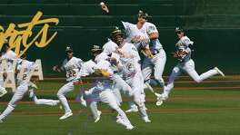 A multiple exposure photograph of Oakland Athletics' Chad Pinder (18) and Ramon Laureano (22) as Pinder catches a ball hit by Seattle Mariners' Dee Gordon (not pictured) as the Athletics hosted the Mariners at the Oakland Coliseum on Sunday, September 2, 2018. The A's won the game 8-2.