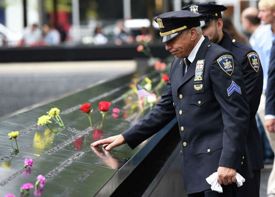 A New York State Court Sergeant looks down into the South Pool during observances on September 11, 2018  held on the 17th anniversary of the September 11, 2001, terror attacks at the annual ceremony at the Ground Zero memorial site. (Photo by TIMOTHY A. CLARY / AFP)TIMOTHY A. CLARY/AFP/Getty Images Photo: TIMOTHY A. CLARY / AFP or licensors