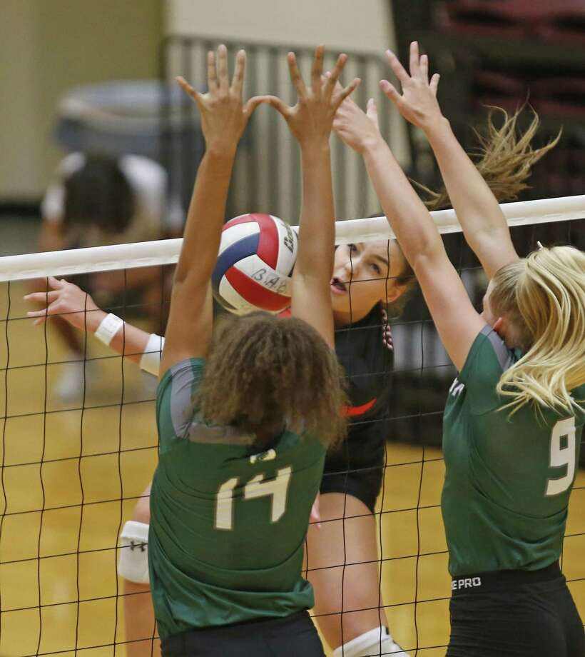 Caroline Meuth slams the ball past Kina Mond,L and Carlee Pharris from the District 27-6A high school volleyball showdown between rivals Churchill and Reagan on Tuesday, September 11, 2018. Photo: Ronald Cortes, Photo Correspondent / 2018 Ronald Cortes