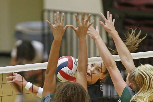 Caroline Meuth slams the ball past Kina Mond,L and Carlee Pharris from the District 27-6A high school volleyball showdown between rivals Churchill and Reagan on Tuesday, September 11, 2018.