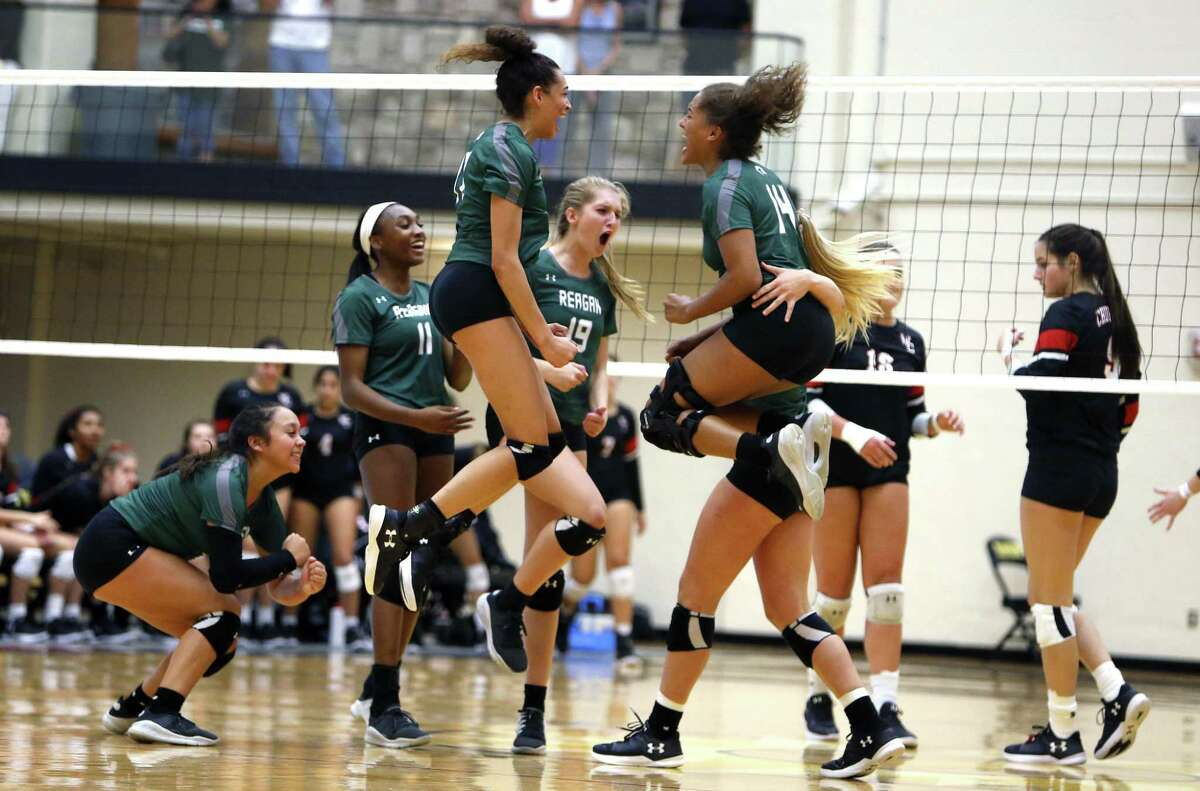 Reagan celebrates after winning the final match from the District 27-6A high school volleyball showdown between rivals Churchill and Reagan on Tuesday, September 11, 2018.