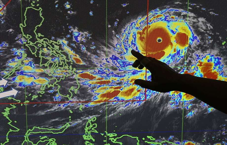"Filipino forecaster Meno Mendoza illustrates the path of Typhoon Mangkhut, locally named ""Typhoon Ompong"" as it approaches the Philippines with sustained winds of 127 miles per hour and gusts of up to 158 mph, at the Philippine Atmospheric, Geophysical and Astronomical Services Administration in metropolitan Manila, Philippines on Wednesday, Sept. 12, 2018. Philippine officials say they plan to evacuate thousands of villagers, shut down schools and offices and scramble to harvest rice and corn as the most powerful typhoon so far this year menacingly roars toward the country's north. Photo: Aaron Favila, Associated Press"