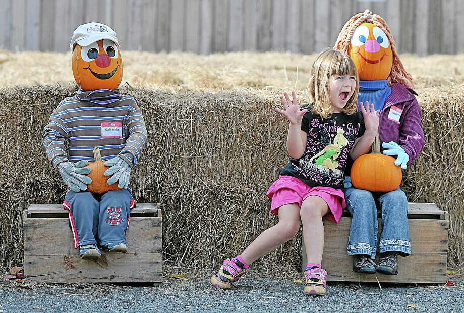 A girl grabs a seat next Bernice and Ernie Acorn at Pumpkintown at Paul & Sandy's Too in East Hampton. Photo: File Photo / TheMiddletownPress