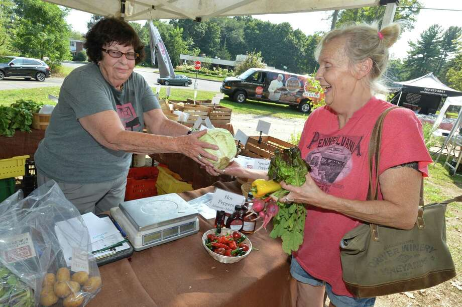 Carol Negeli buys some vegeatbles from Jo DeMenna like cabbage, peppers and lettuce all picked fresh from the Ambler Farm stand at the Wilton Farmers Market on Wednesday September 5, 2018 in Wilton Conn. Photo: Alex Von Kleydorff / Hearst Connecticut Media / Norwalk Hour